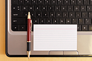 Blank Index Card with Pen on laptop Computer